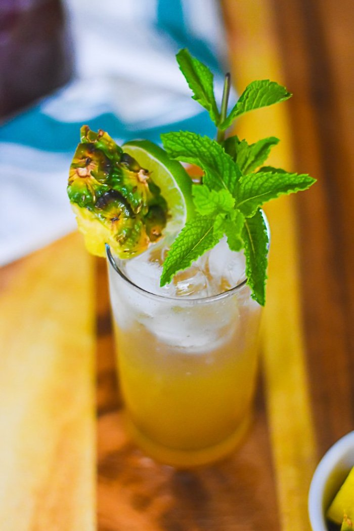 brown sugar pineapple mojito cocktail on wooden cutting board.