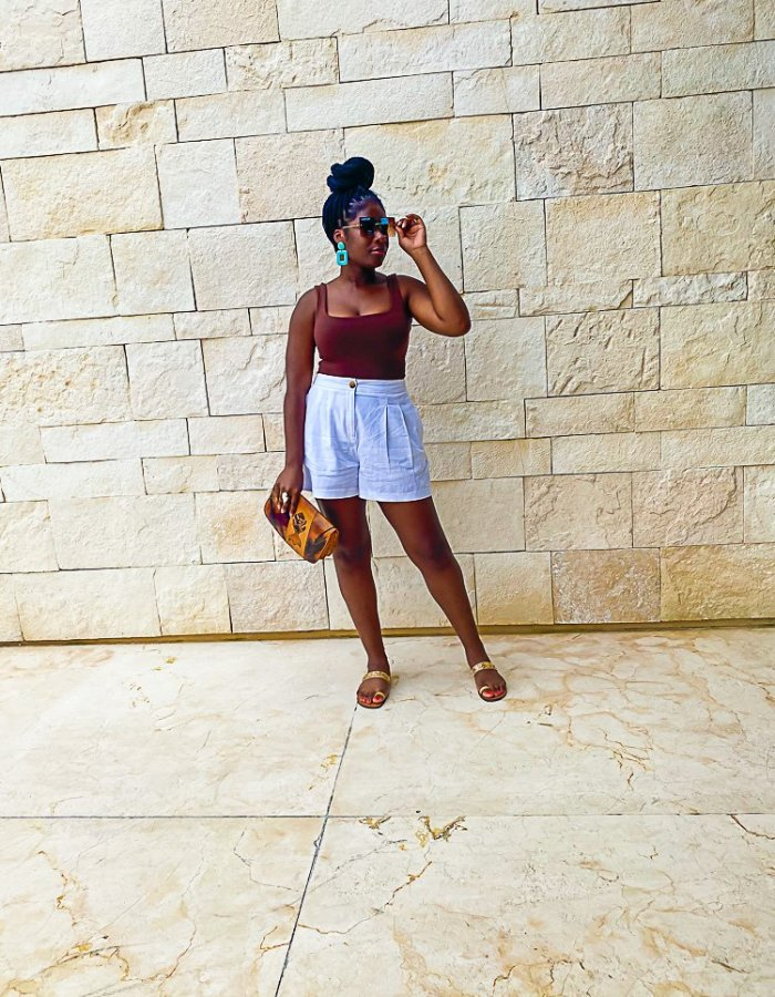 Jazzmine standing outside in white linen shorts and a brown tank top.