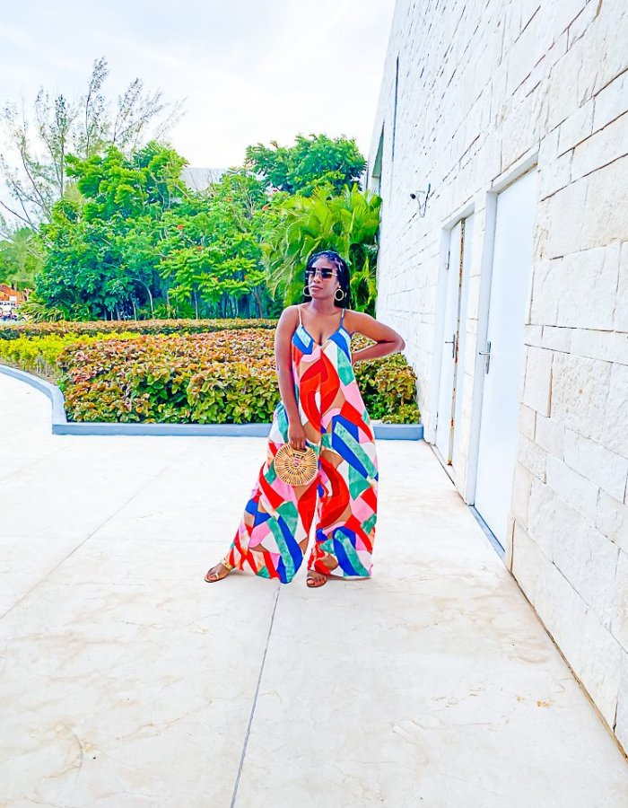 Jazzmine standing outside hotel wearing colorful, geometric patterned jumpsuit.
