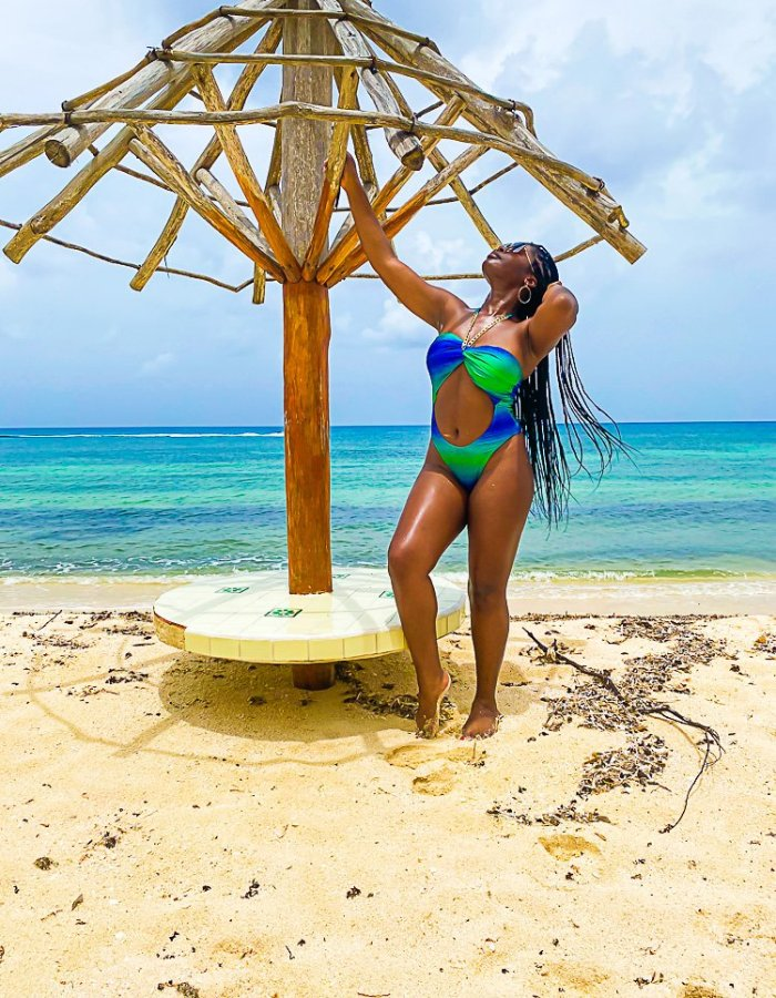 Jazzmine on beach in Cozumel, wearing green and blue cutout bathing suit.