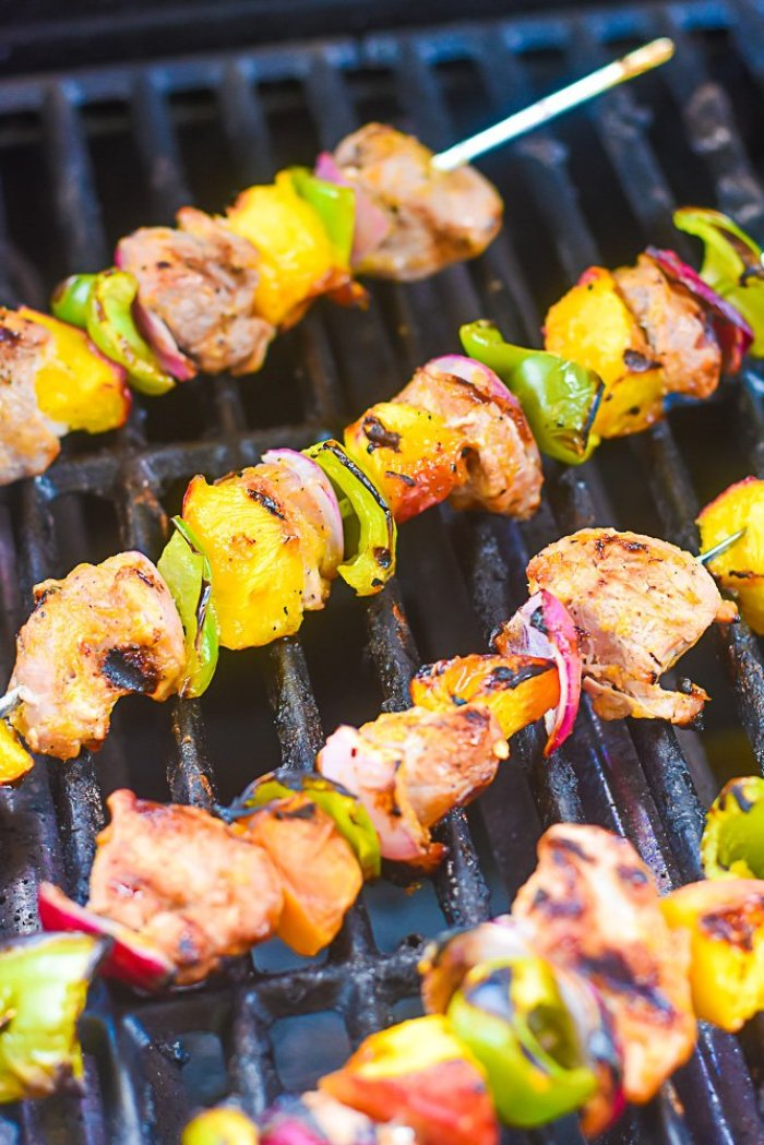 pork and produce skewers cooking on gas grill.