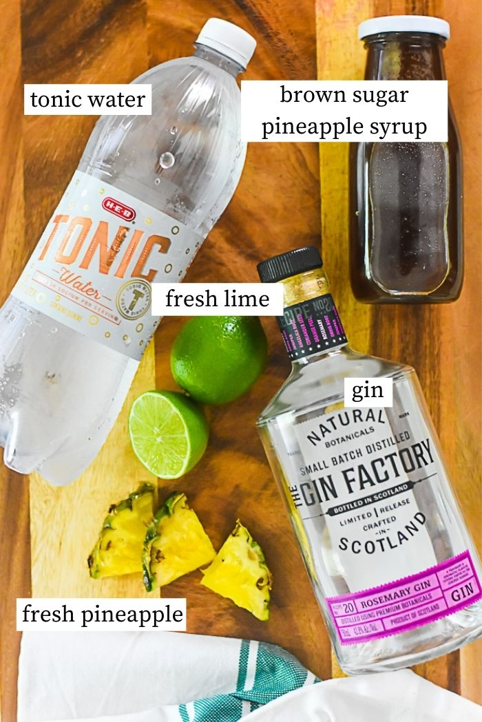flat lay of bottle of gin, wedges of fresh pineapple, bottle of brown sugar syrup, fresh limes, and bottle of tonic water on wooden countertop.