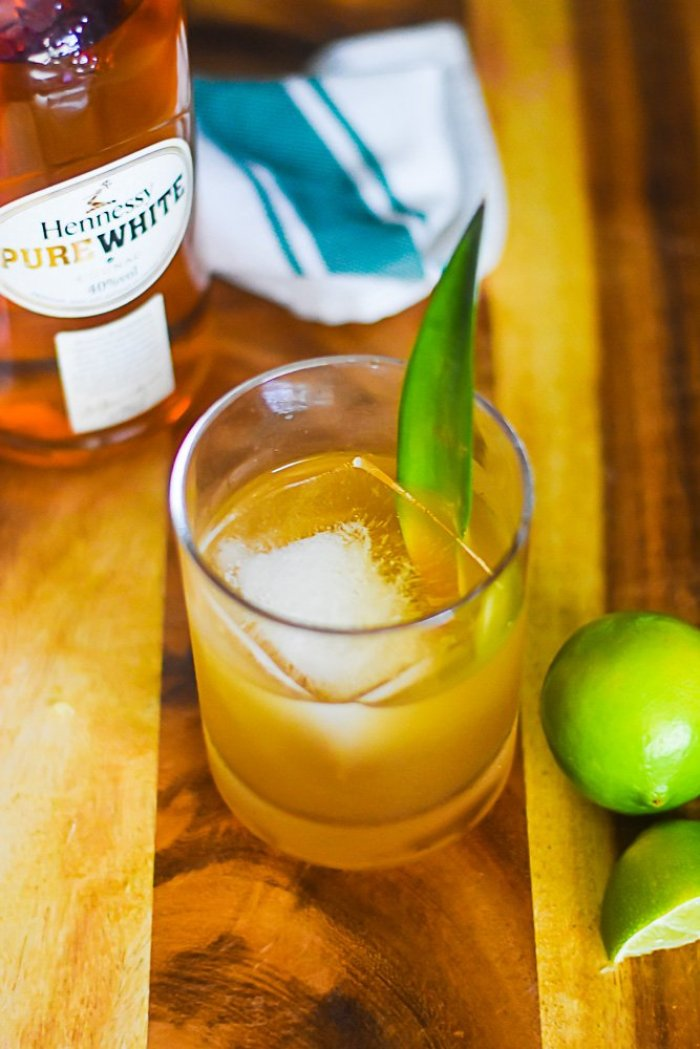 hennessy pure white cocktail on ice, garnished with pineapple frond.