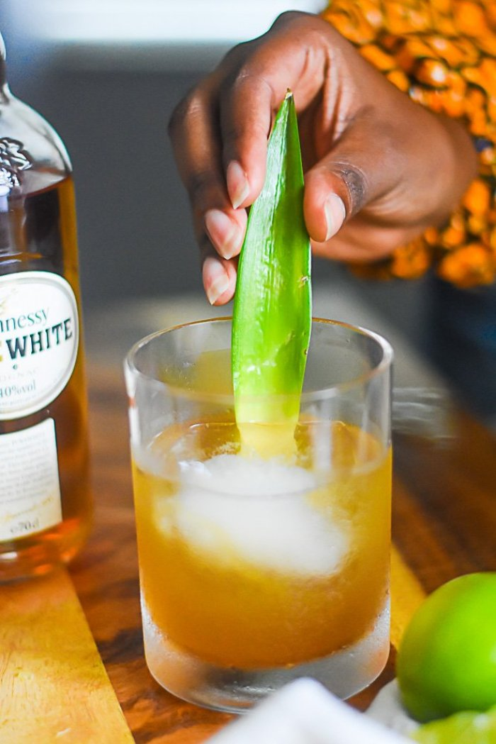 adding pineapple frond to finished white cognac cocktail in rocks glass.
