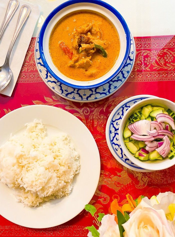 bowl of panang curry, plate of rice, and bowl of Thai cucumber salad on red tablecloth.