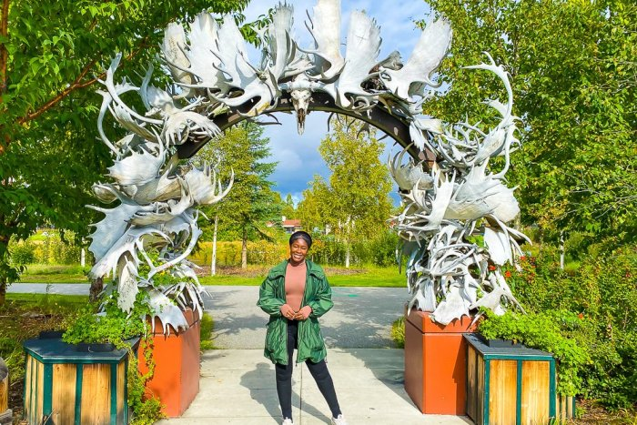 Jazzmine standing under antler arch at Fairbanks, Alaska visitors center.