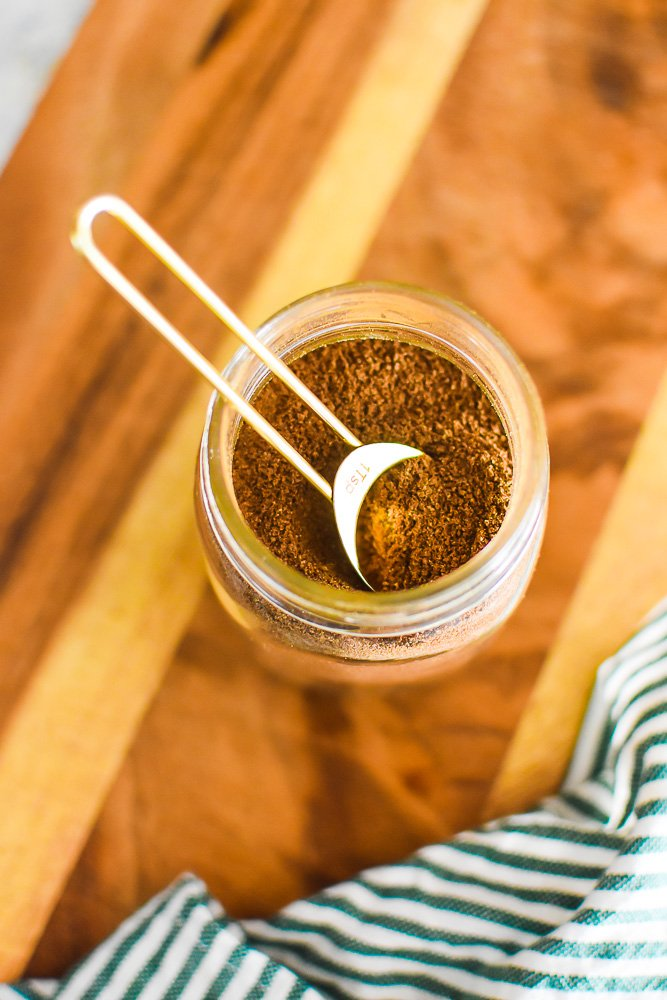 clear jar filled with chai spice blend and golden measuring spoon on top.