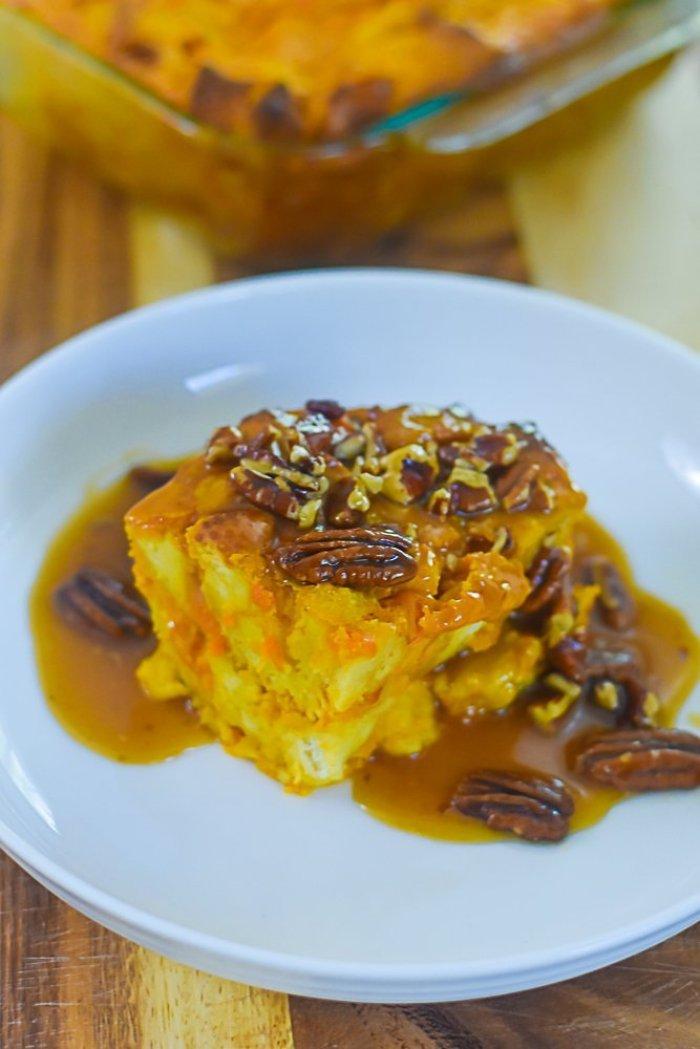 chunk of sweet potato praline bread pudding on white plate.