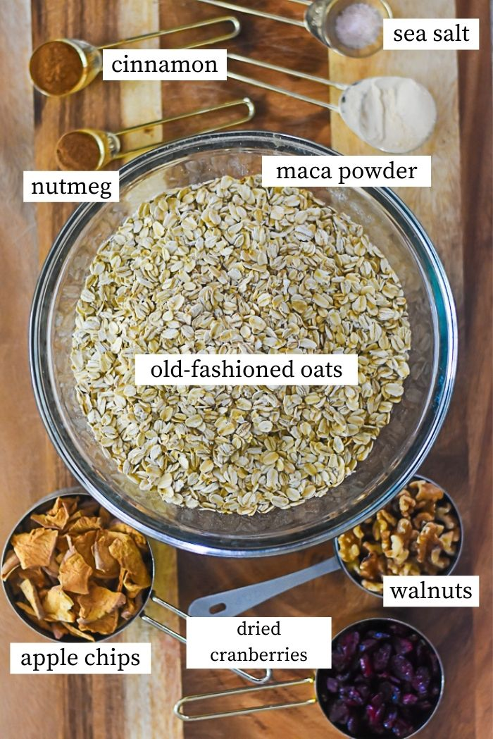 labeled flat lay of homemade instant oatmeal ingredients: apple chips, dried cranberries, walnuts, rolled oats, nutmeg, cinnamon, sea salt, and maca powder.