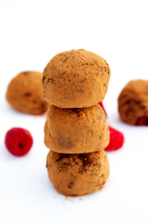 Rich Dark Chocolate Raspberry Truffles are an easy, elegant dessert made with only 5 ingredients. These are perfect for your next holiday get-together..- Stack of finished truffles on white table with fresh raspberries