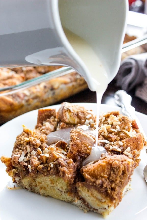 Overnight Coconut Cinnamon Pecan French Toast Casserole - Elevate your morning breakfast with this deliciously easy, make-ahead-breakfast casserole.- White saucer with sauce, white plate, metal fork