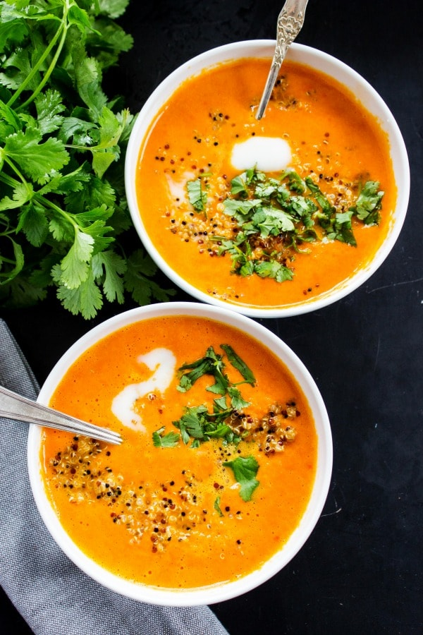 Thai Curry Red Pepper Quinoa Soup is an easy 30-minute meal made with red curry, coconut milk and quinoa. Skip take-out and make this healthy twist instead.- Two white bowls, metal spoons, herbs, wooden table