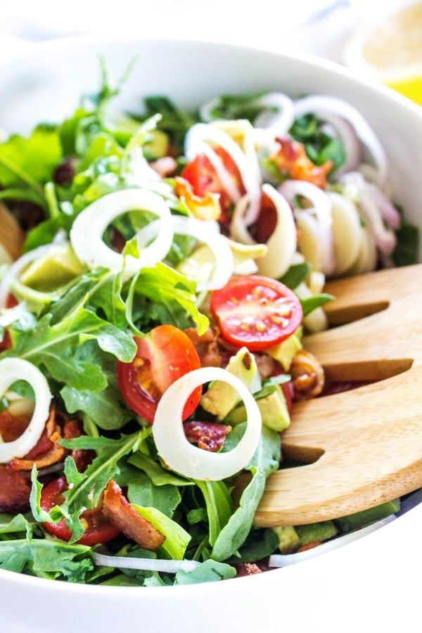 ARUGULA AND HEARTS OF PALM SALAD White bowl, wooden salad spoon