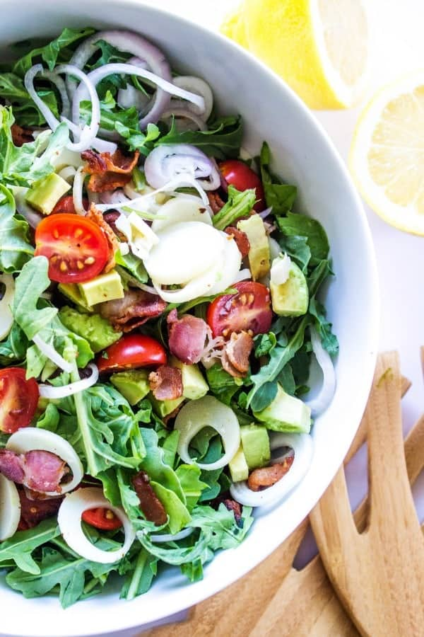 ARUGULA AND HEARTS OF PALM SALAD in white bowl with wooden salad spoons
