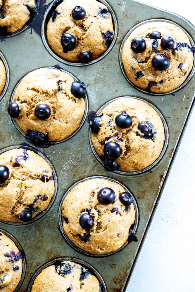 Simple and easy we love these {HEALTHIER} BANANA BLUEBERRY MUFFINS. Made with whole grains, flax seed and blueberries, they make a great breakfast or snack.