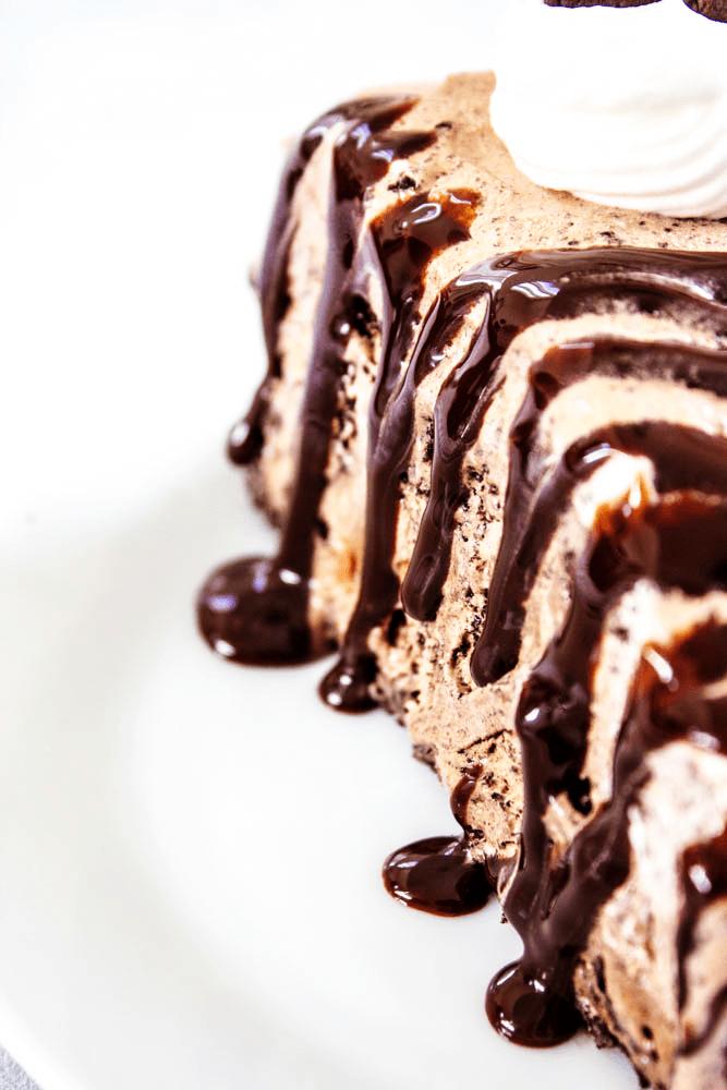 chocolate oreo ice cream cake, hot fudge sauce, whipped cream, white plate