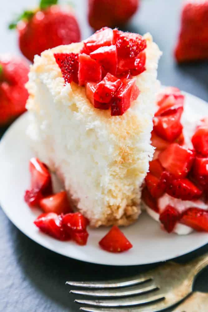 Angel Food Cake topped with strawberries and whipped cream on white plate.