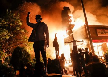 Protestors demonstrate outside of a burning fast food restaurant, early Friday, May 29, 2020, in Minneapolis. Protests over the death of George Floyd, a black man who died in police custody Monday, broke out in Minneapolis for a third straight night. (AP Photo/John Minchillo)