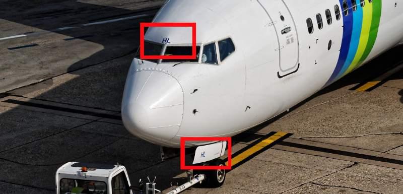 Que signifient les caractères sur la porte du train avant des avions ?