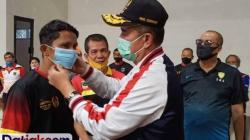 Wagub Sumbar Nasrul Abit didampingi Ketum KONI Sumbar, Syaiful, memasangkan masker kepada salah seorang atlet proyeksi PON XX Papua, saat menjalani latihan bersama di Sport Hall KONI Sumbar, Sabtu (8/8). (Foto: Istimewa)