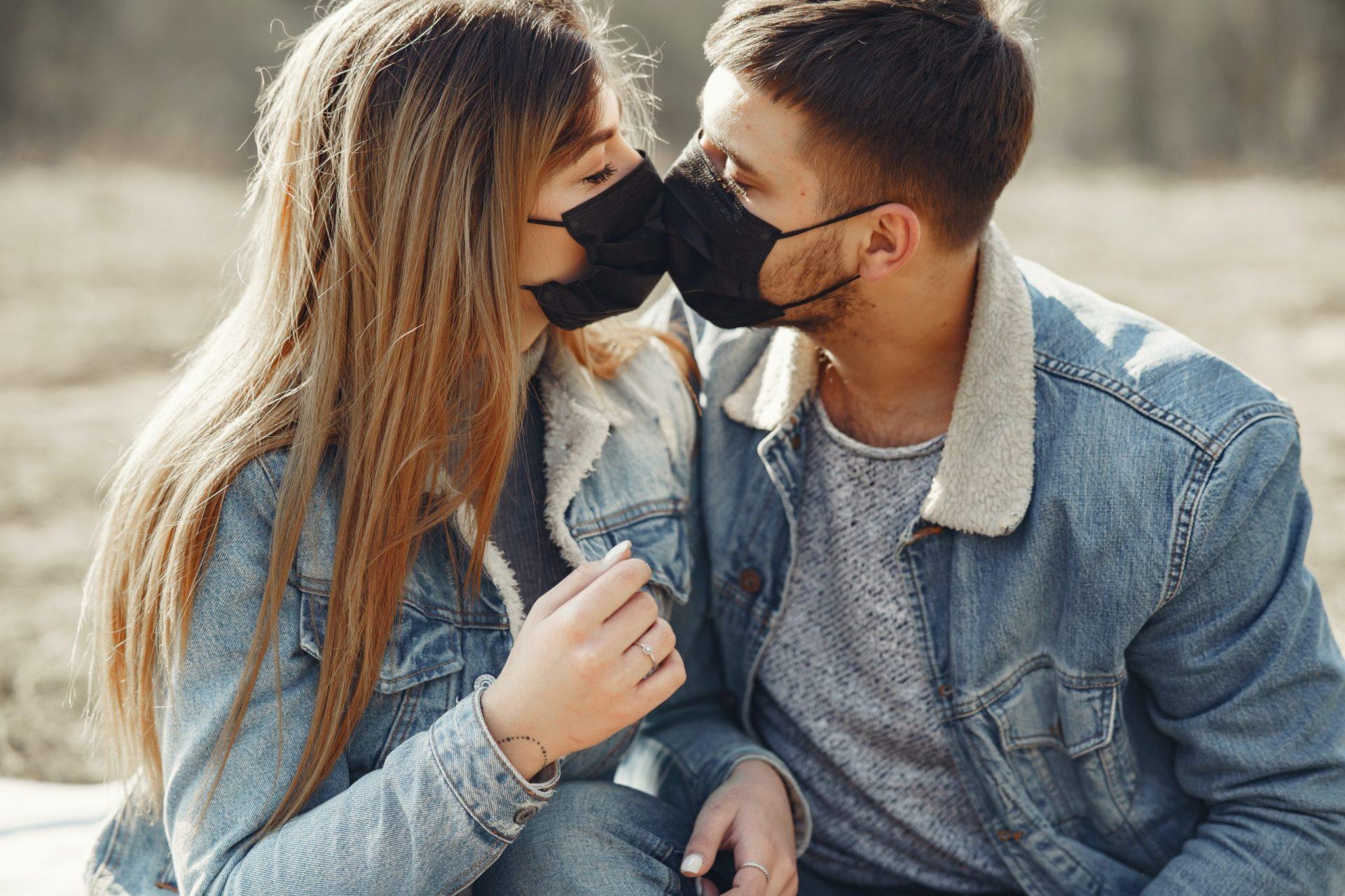 man and woman kissing while wearing covid masks