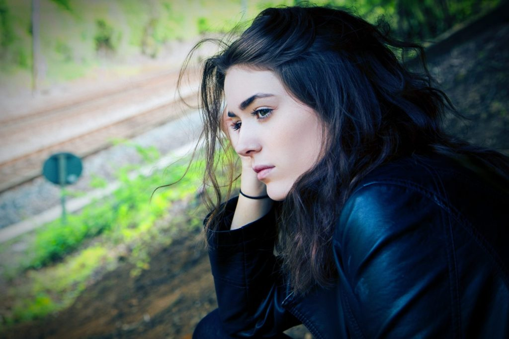 Woman staring out window seemingly with anxiety