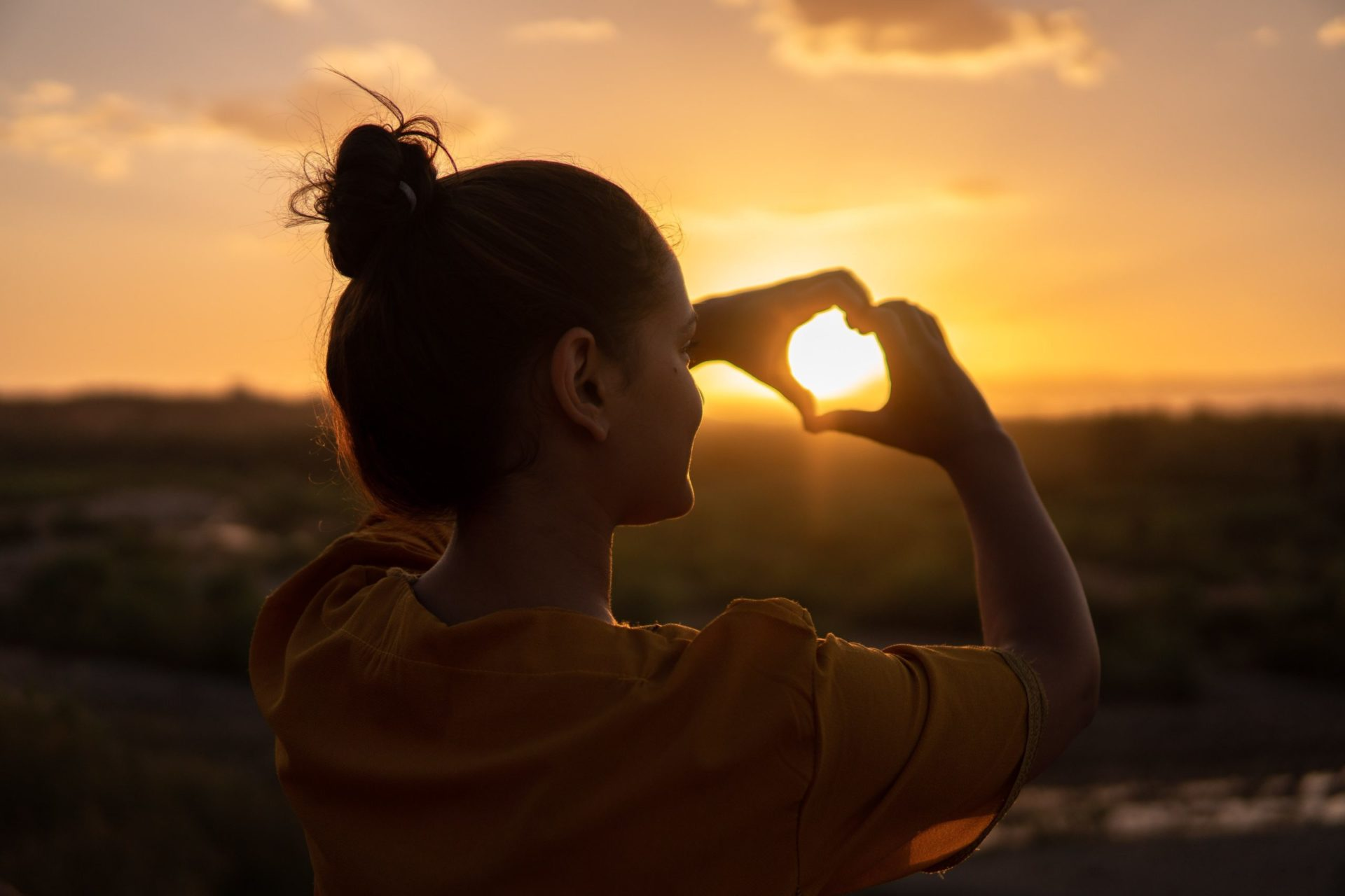 Woman smiling and holding hands in shape of heart in front of sunset