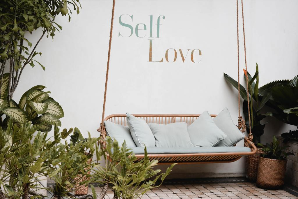 Image of an outdoor patio space with words Self Love on wall