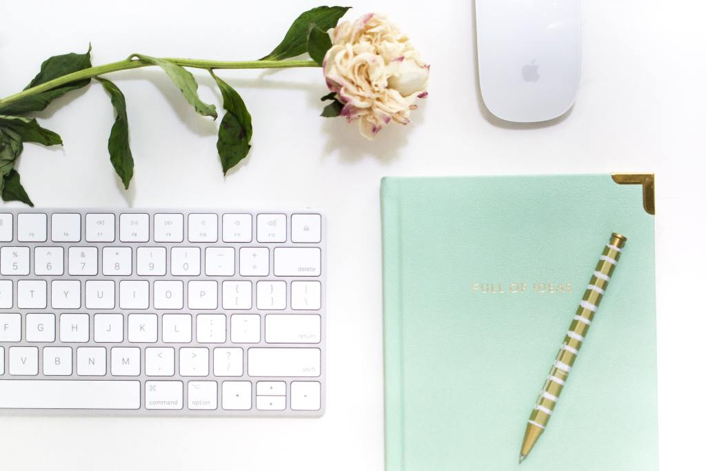 white keyboard with green notebook and flower