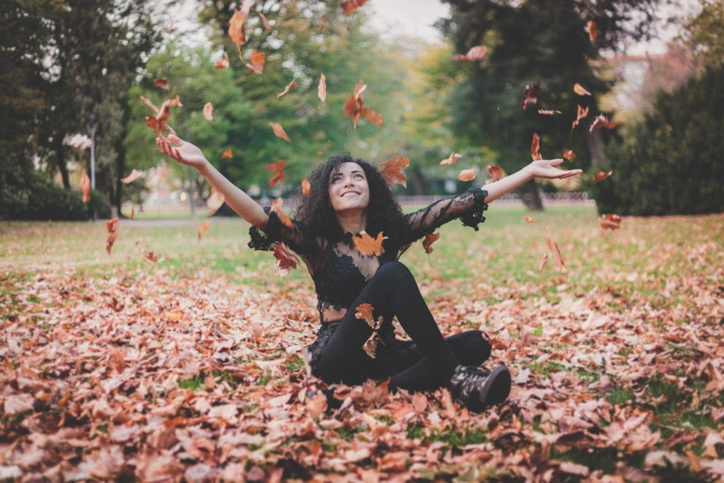 Woman smiling while outside in Fall leaves