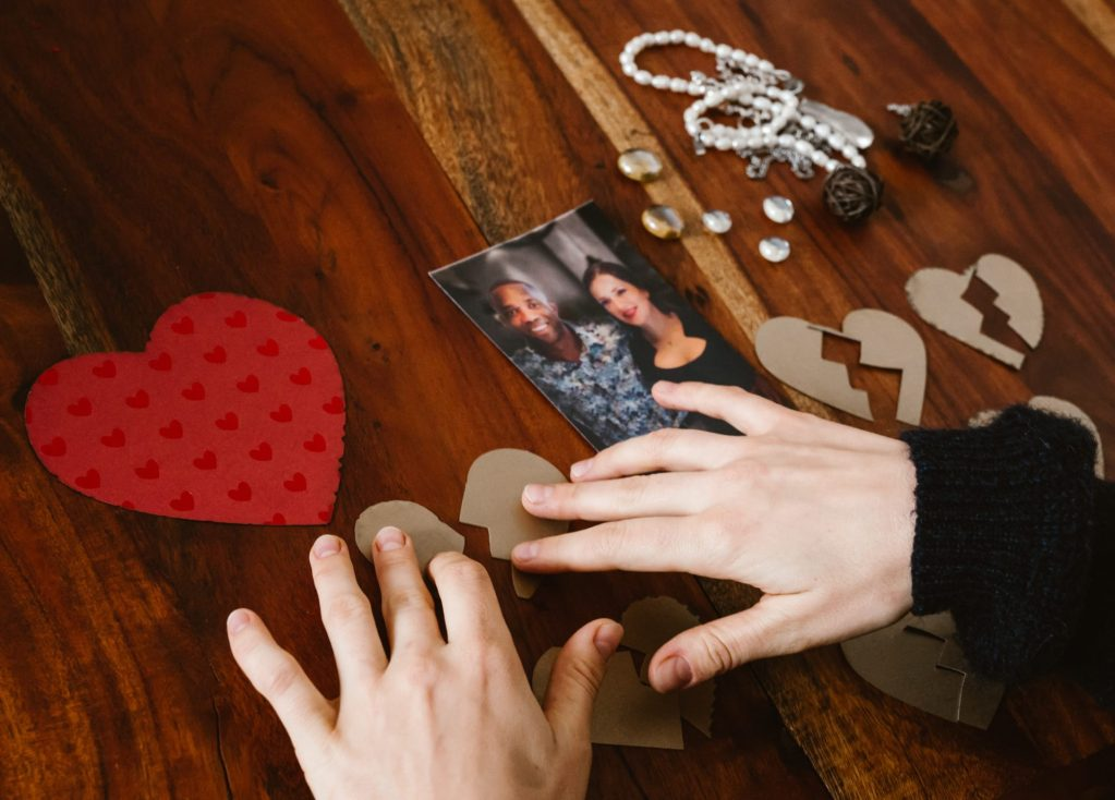 Woman's hands over photo of couple and paper-made broken heart