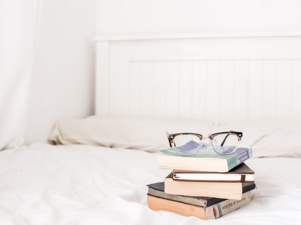 Books and eyeglasses on white bedspread