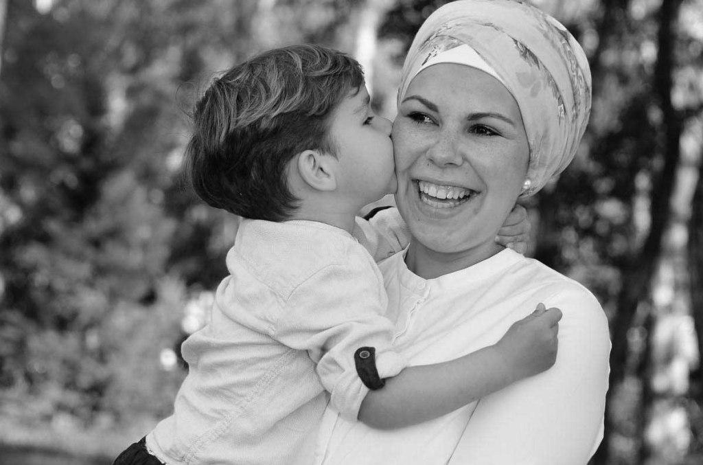 Kind küsst dattelbeere Mama auf die Wange.