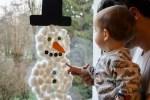 Baby berührt Fensterdekoration aus Watte.