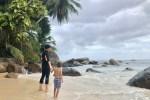 Mama steht händchenhaltedn mit ihrem Sohn am Strand im Wasser