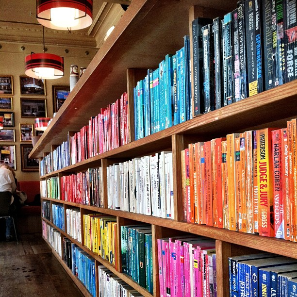 Stacks of color-coded books lining a coffee and liquor bar? Win. #latergram #iceland