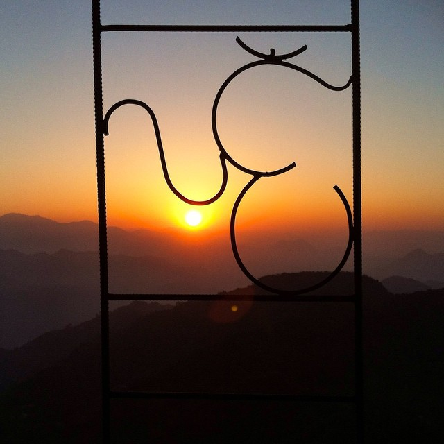 Catching the sunrise high in the mountains, through an Om sign in the fence, naturally.