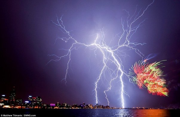 An  electrical storm perfectly complements fireworks launched to  mark Australia Day 2012 celebrations in Perth, in a stunning shot by  Matthew Titmanis