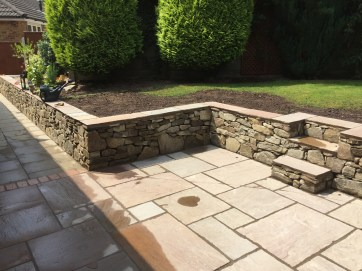 Low retaining wall with dry stone effect. Steps incorporated to reach the higher level