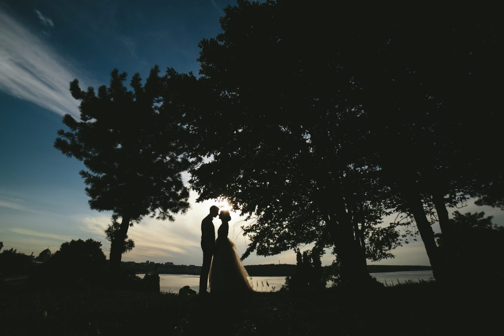 bride groom standing in the park and tenderly looking at each other