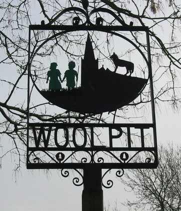 """Sign erected in the village of Woolpit (originally """"Wolf-pit,"""" """"pit for trapping wolves""""), 1977."""
