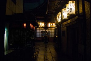 A Japanese alley at night in July with brightly lit lanterns