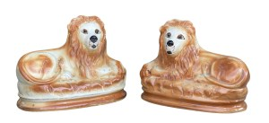Pair of Staffordshire Pottery Lions seated on an oval plinth base.