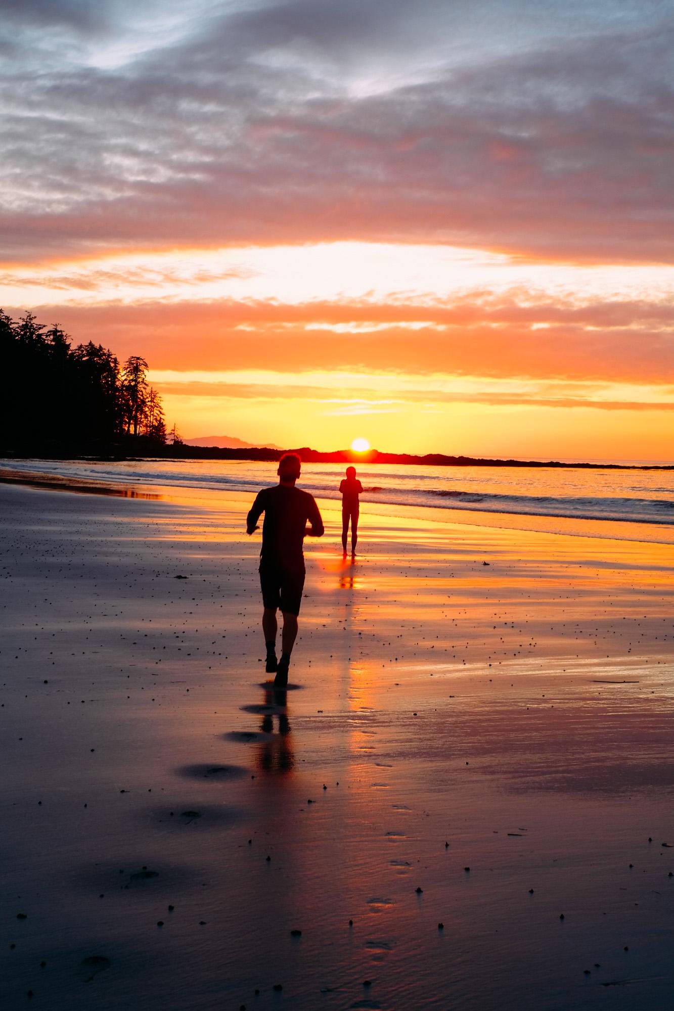 A man runs to his woman while the sun sets at Cape Scott.