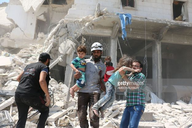 Syrian civilians and a rescue worker evacuate children in the Maadi district of eastern Aleppo after regime aircrafts reportedly dropped explosive-packed barrel bombs on August 27, 2016. At least 15 civilians were reported killed when two bombs fell several minutes apart, near a tent where people were receiving condolences for those killed this week. ALHALBI