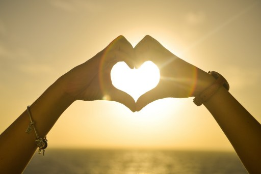 Friends hands together forming a heart in front of sunlight.