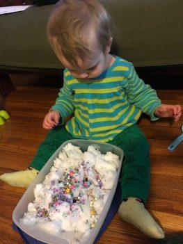child playing in sensory bin