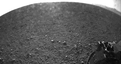 """Curiosity Snaps Picture of Its Shadow This is one of the first images taken by NASA's Curiosity rover, which landed on Mars the evening of Aug. 5 PDT (morning of Aug. 6 EDT). It was taken through a """"fisheye"""" wide-angle lens on one of the rover's front Hazard-Avoidance cameras at one-quarter of full resolution. The camera is the left eye of a stereo pair positioned at the middle of the rover's front side.   The clear dust cover on the camera is still on in this view, and dust can be seen around its edge, along with three cover fasteners. The rover's shadow is visible in the foreground.   As planned, the rover's early engineering images are lower resolution. Larger color images are expected later in the week when the rover's mast, carrying high-resolution cameras, is deployed.   Credit: NASA/JPL-Caltech"""