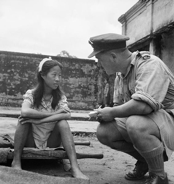 A Chinese girl from one of the Japanese Army's 'comfort battalions' sits on a stretcher, awaiting interrogation at a camp in Rangoon. The uniform and insignia on the shoulder of the man next to her indicates that he is a Flying Officer in the Royal Air Force.