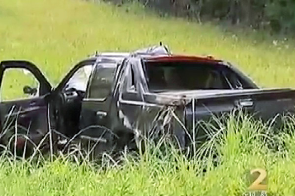 In this image taken from video, an SUV sits off road at the scene of a car crash involving former NBA All-Star guard Mookie Blaylock on Friday outside Atlanta.
